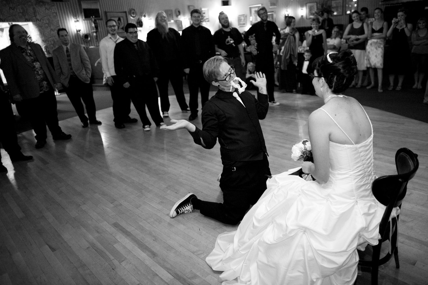 A groom throws his hands back just after he has pulled the garter off his brides' leg.