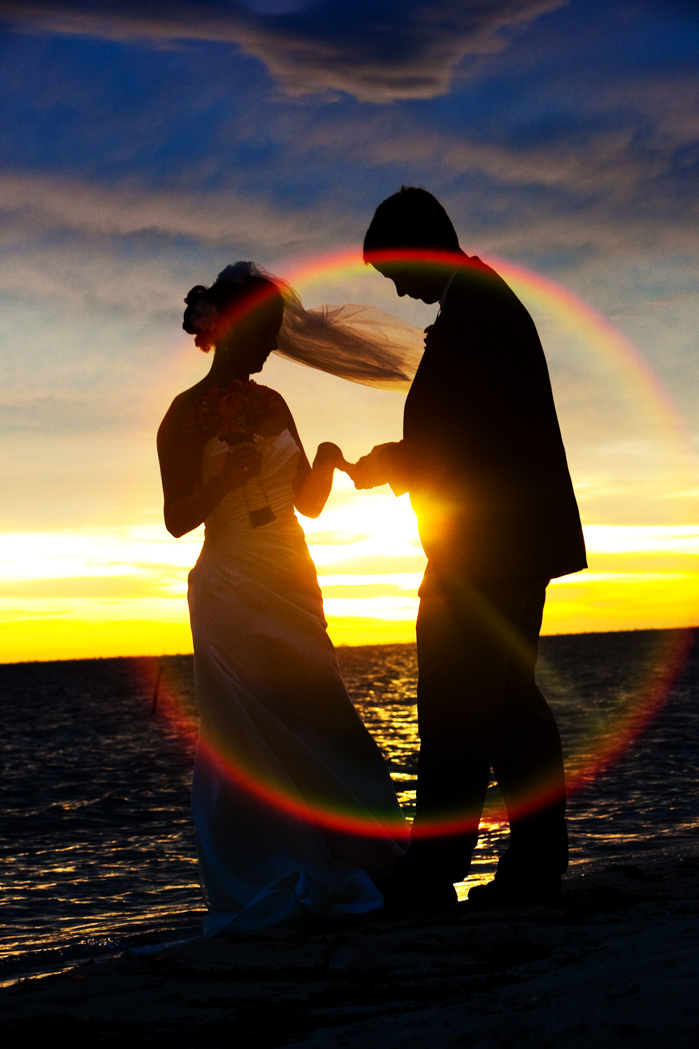 A bride shows her groom the combination of her engagement and wedding rings as a phenomenal sunset happens at Zama Beach Club on Isla Mujeres, Mexico.