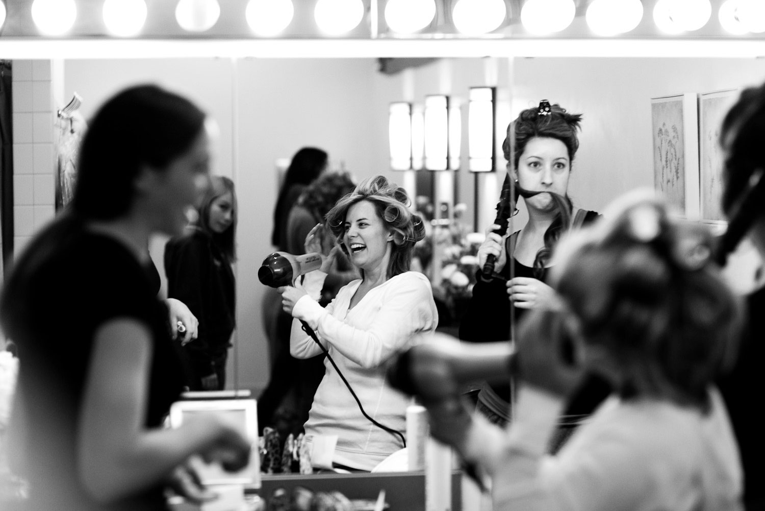 A wedding image of a happy bride getting ready with her bridesmaids.