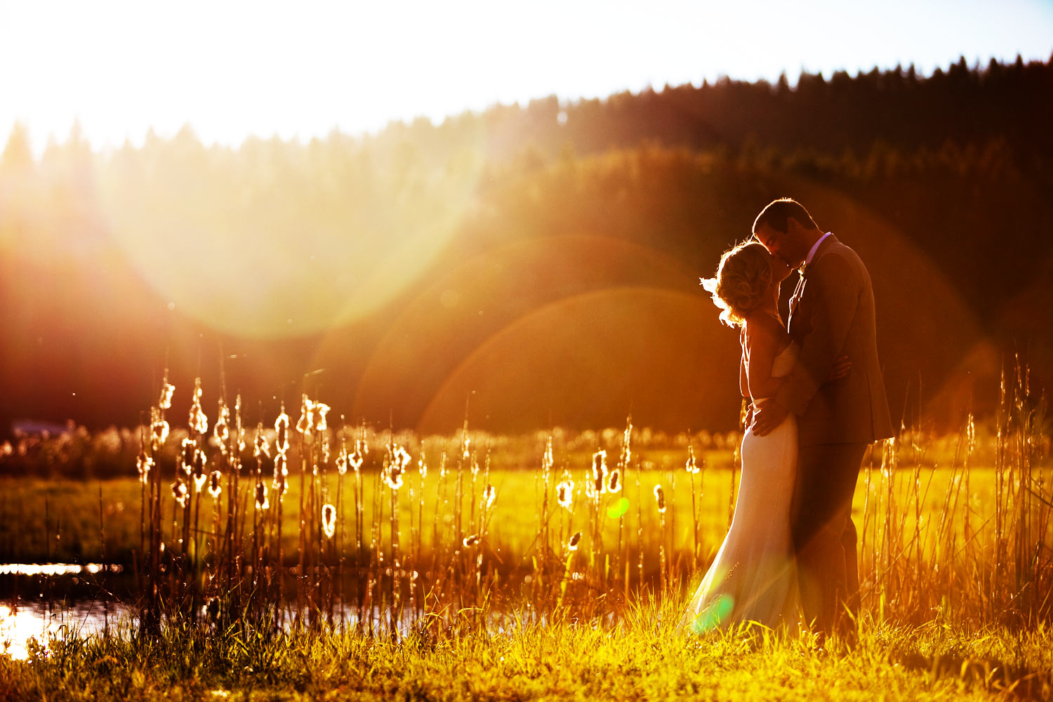 A bride and her groom kiss for their wedding photographer during a portrait session in front of the setting sun in McCall, Idaho.