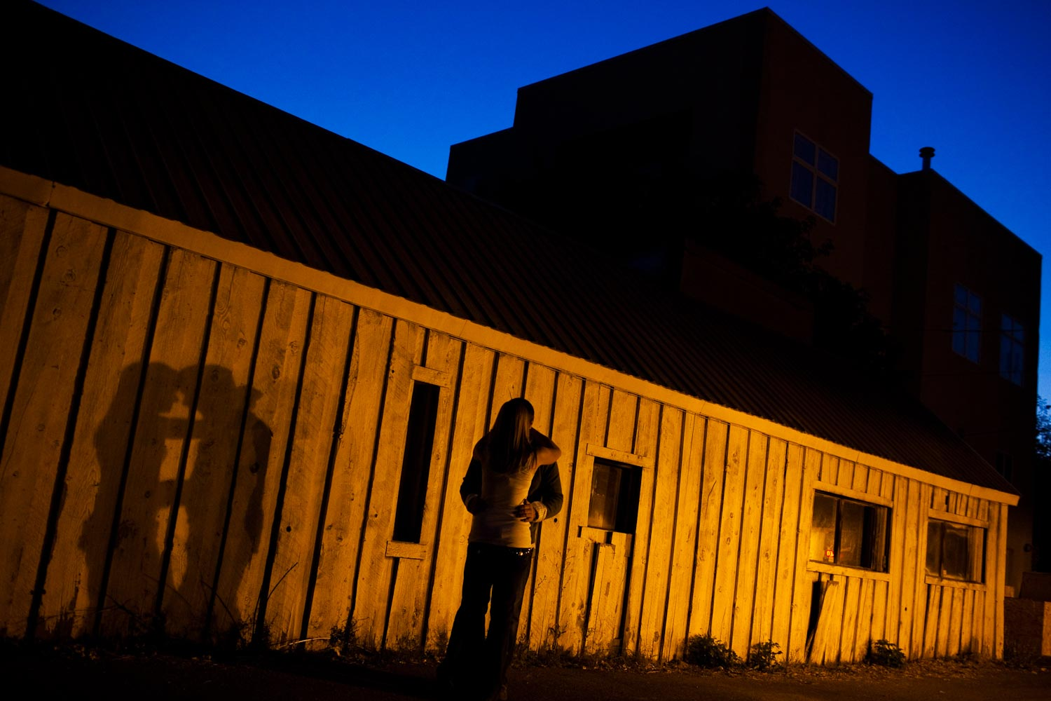 A night photograph of an engaged couple who have stopped for a kiss in an alley in Ketchum, Idaho.