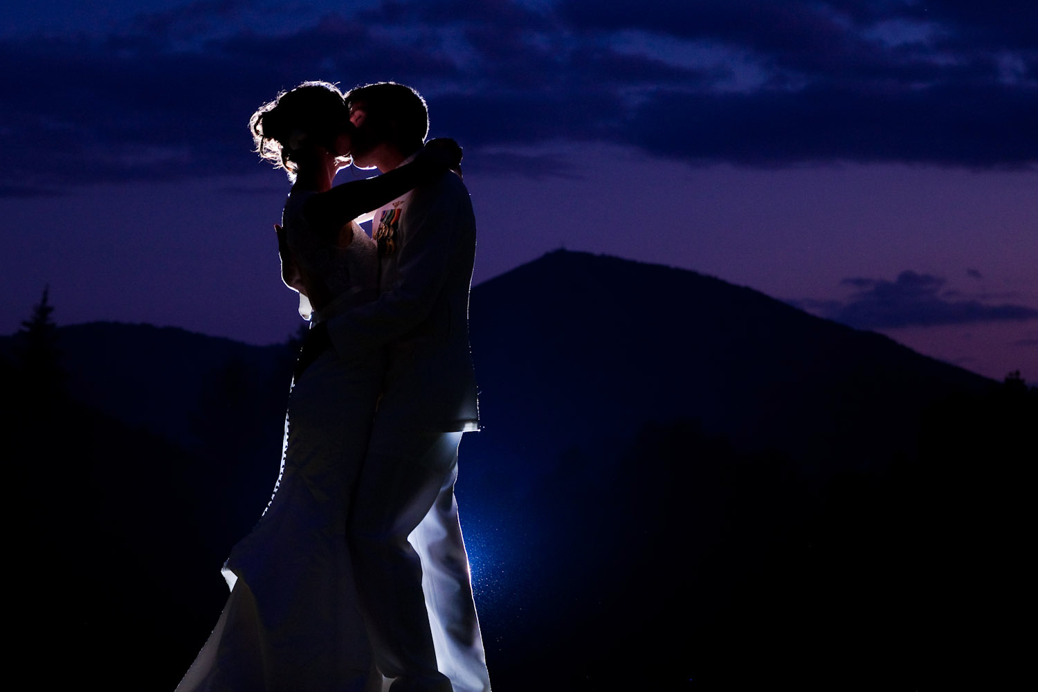 A wedding portrait of a bride and groom, backlit by a strobe, at dusk with the silhouette of a mountain behind them.