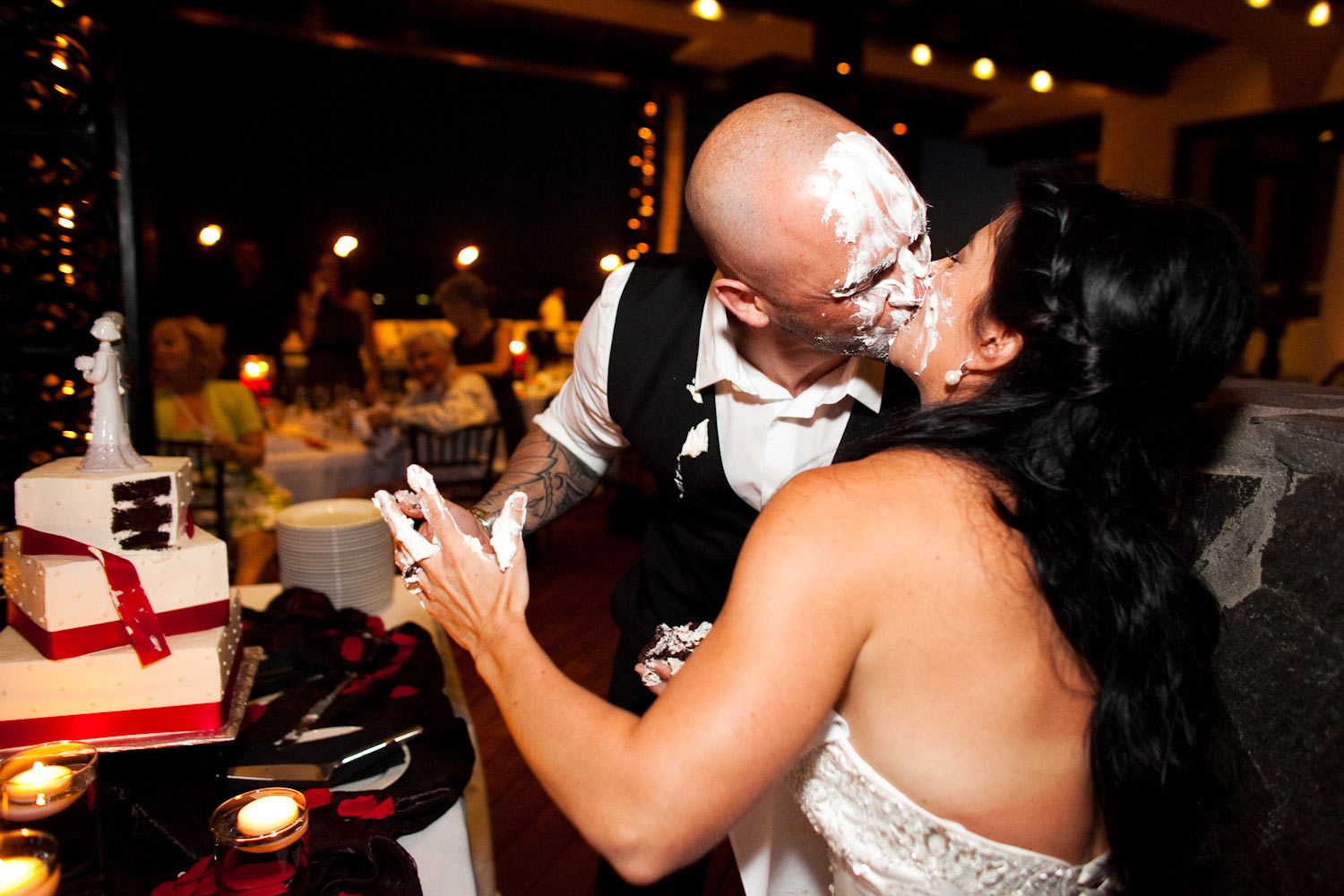 Bride and Groom kiss after smooshing their wedding cake in their faces.  Photograph by Craig Wolfrom.