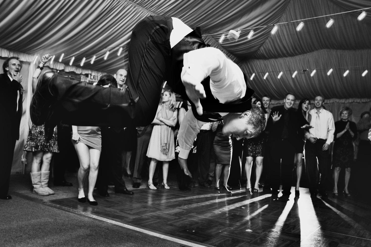 A Groomsman takes flight above the reception dancefloor.  He is about to do the worm!  Wedding photography by Craig Wolfrom.