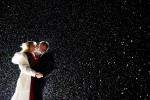 A portrait of a bride and groom, back lit, with a million snow flakes illuminated around them.