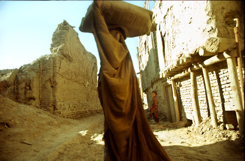 Almost as though she is part of the mud and earth landscape surrounding her, an Afghan woman in her burka walks through a crumbling and destroyed neighborhood inside the capital of Kabul.©Thomas James Hurst