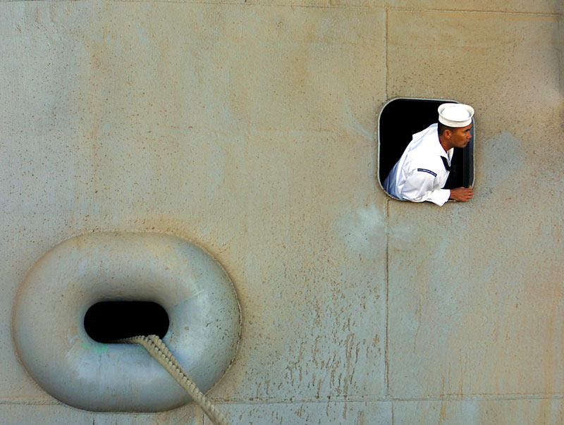 A navy seaman aboard the U.S.S Lincoln hangs outside a porthole as the aircraft carrier returns from a long deployment in the Persian Gulf.©Thomas James Hurst/The Seattle Times