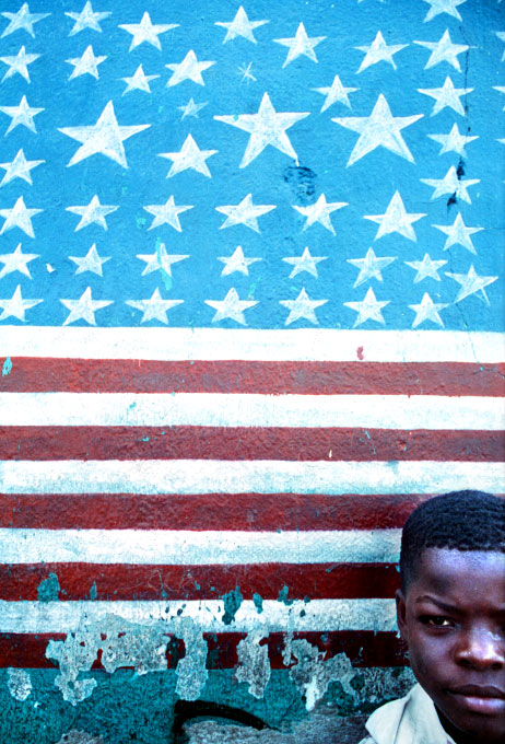 A Haitian boy rests against a wall painted as an American flag in Port-au-Prince's Citi Soleil slum.©Thomas James Hurst