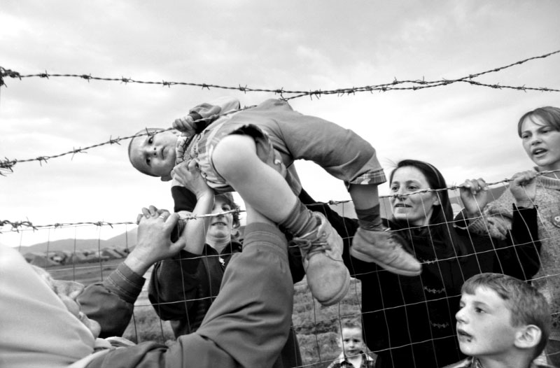 Family members separated in while fleeing the fighting in Kosovo, pass their children through the barbed wire when they are reunited at a refugee camp in northern Albania. ©Thomas James Hurst