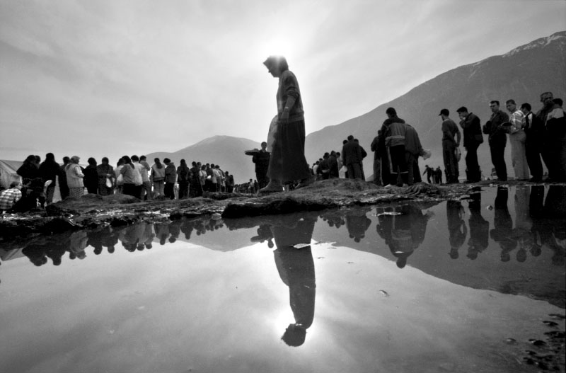 Kosovar refugees stand in mud and water waiting to receive their day's ration of food.©Thomas James Hurst