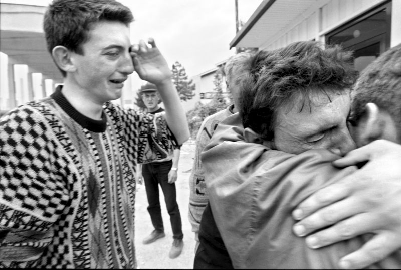 A young man, right, facing out, who was detained by Serb paramilitary inside Kosovo is reunited with his family across the border in Albania.©Thomas James Hurst