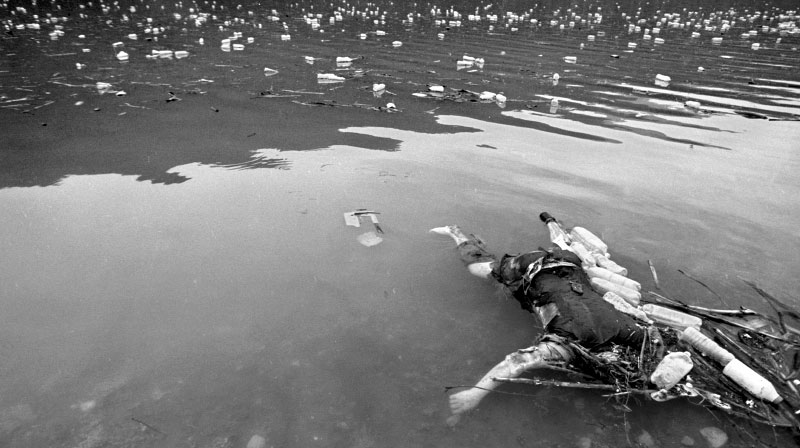 The beheaded body of a Kosovar man floats among the trash in a river running from Kosovo into Albania. Serb paramilitary, carrying out a campaign of ethnic cleansing, murdered men of fighting age and dumped them in rivers and shallow graves. ©Thomas James Hurst