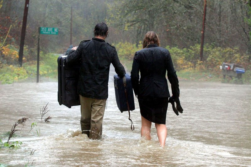 Carrying empty suitcases, Scott Wilson and his wife, Erica Fisette, prepare to wade across Tolt River Road so that they might fill their suitcases with belongings and evacuate their home.©Thomas James Hurst/The Seattle Times