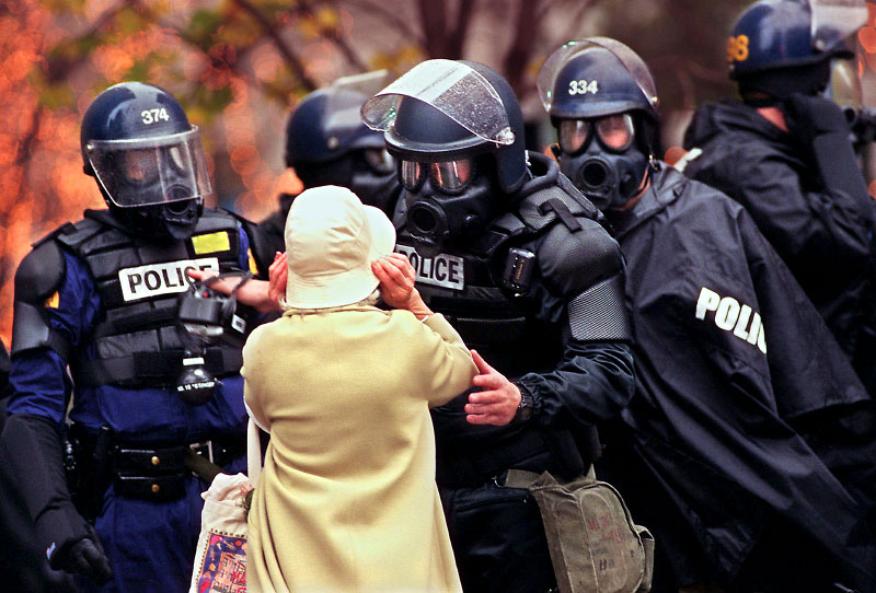A Seattle police officer attempts to help an elderly woman get out from the middle of a demonstration that has turned riotous outside a meeting of World Trade Organization members.©Thomas James Hurst/The Seattle Times