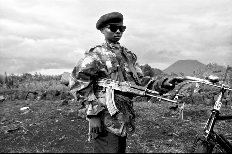 "A 13-year-old member of Zaire's Mi-Mi (""my-my"") Tribe poses with his bicycle andAK-47 assault rifle.©Thomas James Hurst"