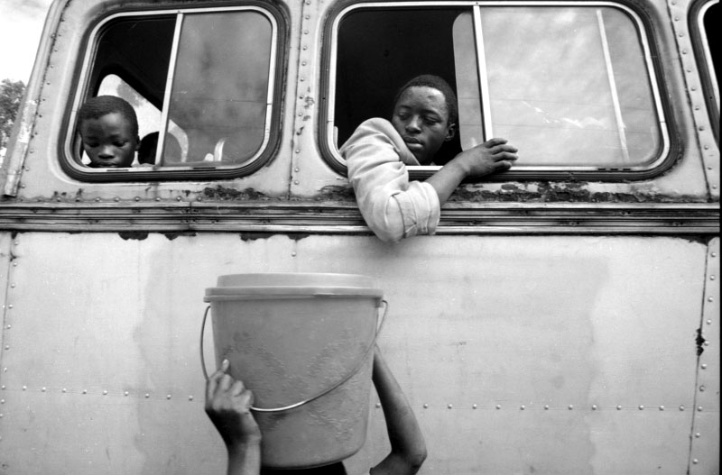 Passengers on a bus leaving Zaire watch as other refugees prepare to board.©Thomas James Hurst