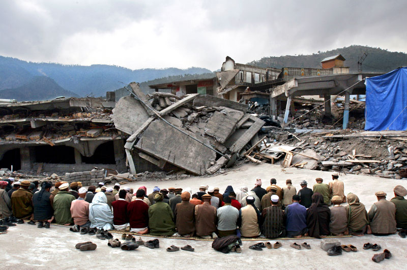 Men pray on what was once the roof of a four-story mosque in the Pakistan city of Balakot. Mohammed Nazir, the mosque's imam said, {quote}God has tested us this time. There is something better in the future.{quote} And yet others in Balakot felt that God was punishing them.©2005-2006 Thomas James Hurst/The Seattle Times