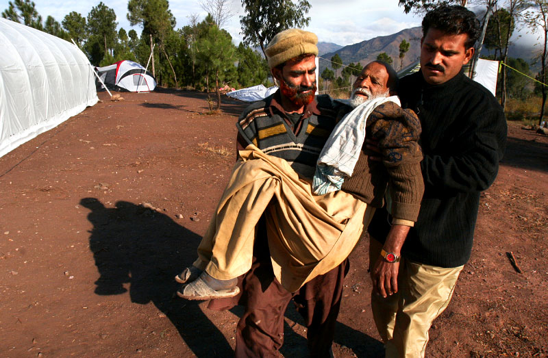 Relatives carry Sheik Kala Khan, 75, to the Human Development Foundation's base-camp hospital. Now, two months after the quake, camp doctors are seeing more routine cases than traumatic ones - infections instead of broken legs.©2005-2006 Thomas James Hurst/The Seattle Times