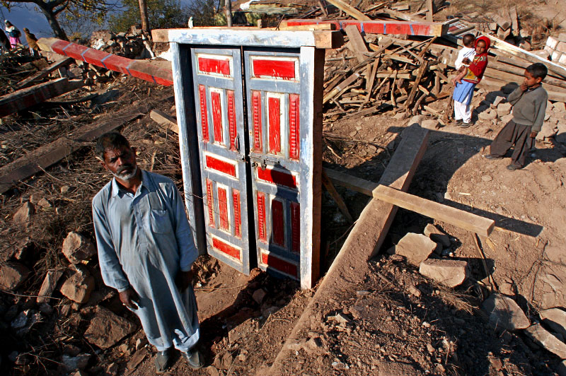 Maboob Khan stands next to his front door - all that remains of his house, one of thousands that dotted village mountainsides, but are now piles of rubble or too damaged to inhabit.©2005-2006 Thomas James Hurst/The Seattle Times