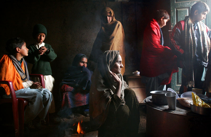 Hafeeza Zaheen, center front, keeps a small cooking fire burning in her livestock stable, where family members gather for warmth and community. The earthquake that claimed thousands also killed her youngest child, five-year-old daughter, Sultana, and her 9-year-old son Basit, second from the left, who suffers from tuberculosis, may not make it through the winter.©2005-2006 Thomas James Hurst/The Seattle Times