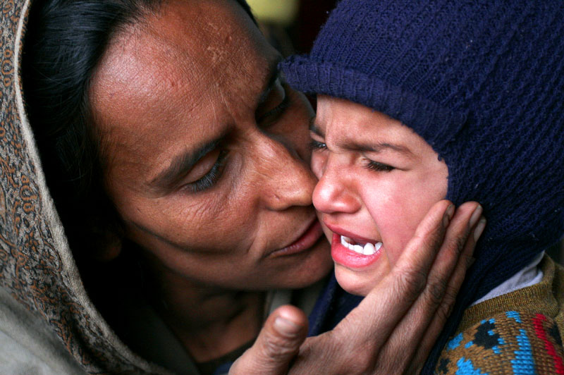 Hafezza Zaheen, who lost her five-year-old daughter, Sultana, in the earthquake, comforts her young nephew Isran Liqat, whose mother was also killed. Liqat, 3, now lives with his father, in his grandfather's home; however, the women in the village of Puthian shower the boy with love and attention.©2005-2006 Thomas James Hurst/The Seattle Times