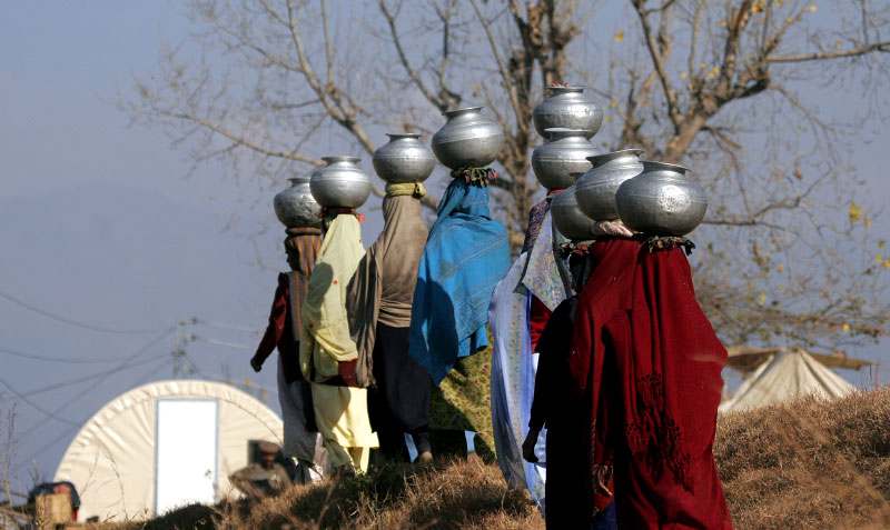 Several times a day, village women trek to a well or mountain stream for water. Members of the Bagam family return to the village with water in silver urns perched atop their heads. Most villagers in the mountainous village of Puthian are living in nylon or canvas tents that were provided after the quake.©2005-2006 Thomas James Hurst/The Seattle Times