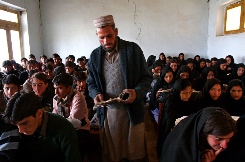 Eighty-three ninth-graders study algebra in a math class taught by Mohammad Idress. An aisle in the middle of the classroom divides the girls from the boys. Classes are being held in some of the less damaged classrooms; however, students must now be squeezed tightly together so that they can share the few desks and books that remain.©2005-2006 Thomas James Hurst/The Seattle Times