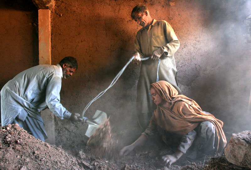 Gul Majeed, center, and his wife, Anyot Jan, remove dirt and rocks from what remains of their home, aided by neighbor Maboob Khan. The couple will use the fragile structure to shelter their cattle and livestock, which are crucial to their own survival.©2005-2006 Thomas James Hurst/The Seattle Times