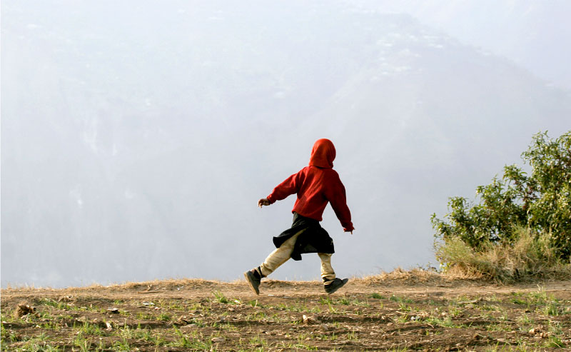 Hafeeza Zaheen's surviving daughter, Muqatas, 7, runs along a footpath in Puthian, were the elevation ranges from 5,000 to 6,700 feet. With winter approaching, temperatures in the mountainous village and across the region will plummet and thousands still lack the proper shelter and food supplies necessary survive.©2005-2006 Thomas James Hurst/The Seattle Times