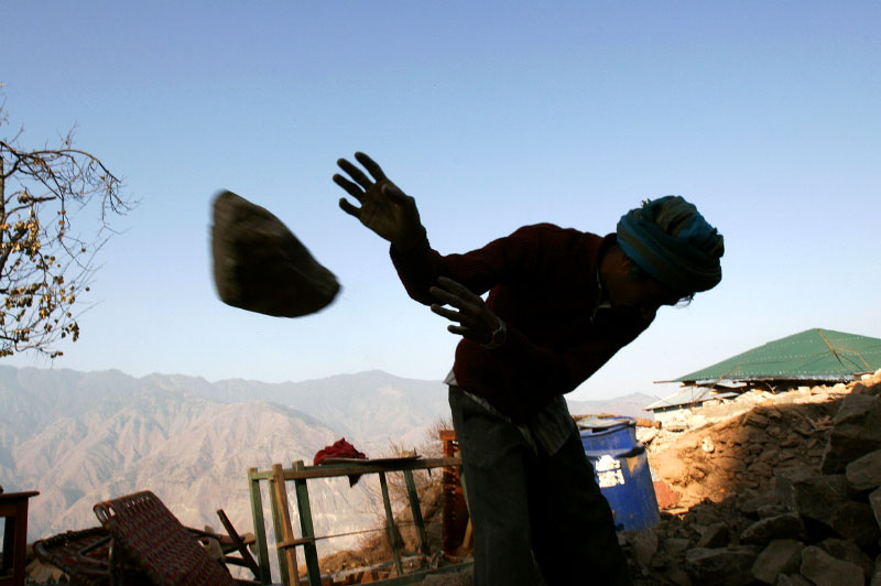 Mohammad Niaz throws stones from a collapsed house into a pile of rocks he'll use to build another home. Almost every house in the village of Puthian was damaged or destroyed.©2005-2006 Thomas James Hurst/The Seattle Times
