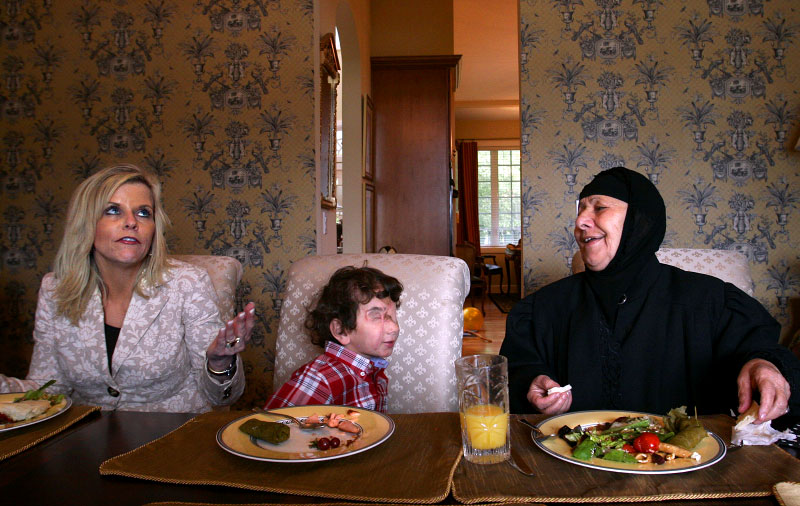 Three-year-old Muhammed sits between his Iraqi grandmother Saudna Ali and his new foster mother Julie Smith at her home in Snohomish. Saudna wanted to see her grandson one last time before she returned to Iraq.