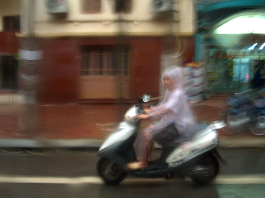 scooter and rider in rainHanoi, Vietnam