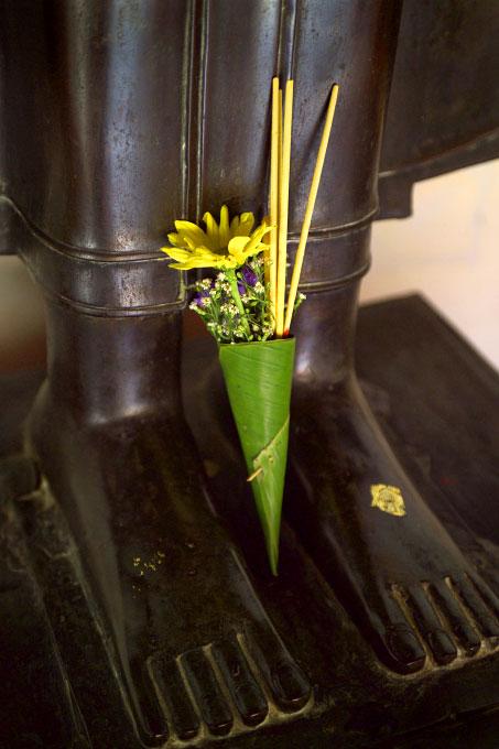 flower offering at a bronze Buddha's feetWat BenchamabophitBangkok, Thailand