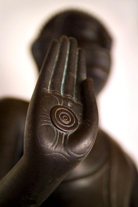 uplifted hand of a bronze BuddhaWat BenchamabophitBangkok, Thailand