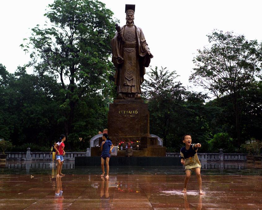 kids playing in rain at monument to Ly Thaito Hanoi, Vietnam
