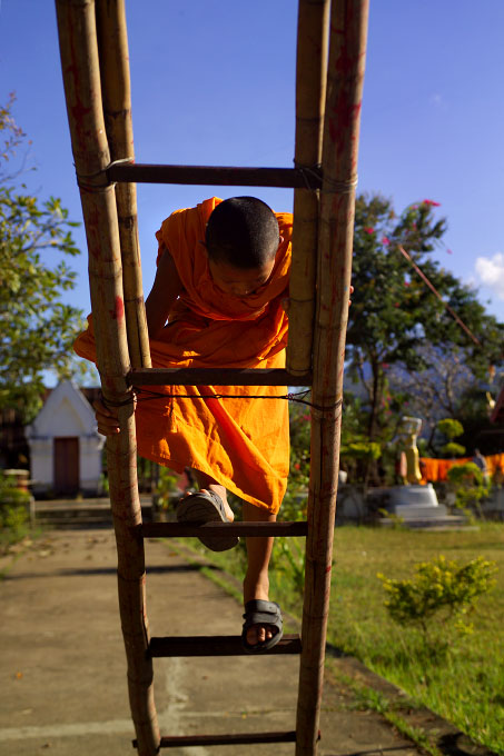 novice monk  on a ladderWat Pha MahathatLuang Prabang, Laos