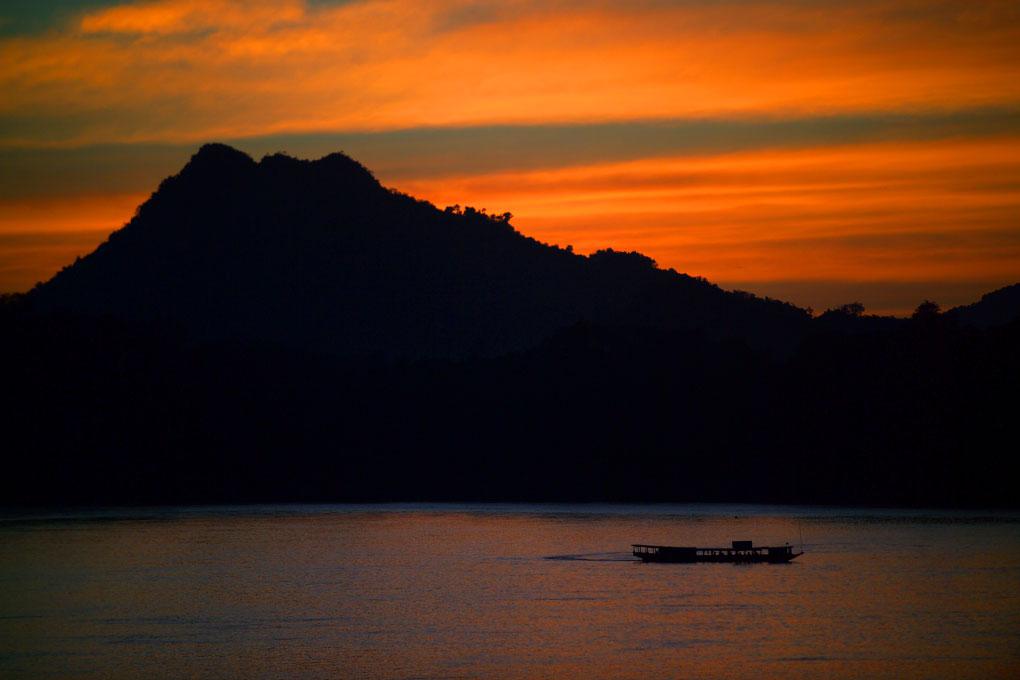longtail ferry crossing the Mekong RiverLaos