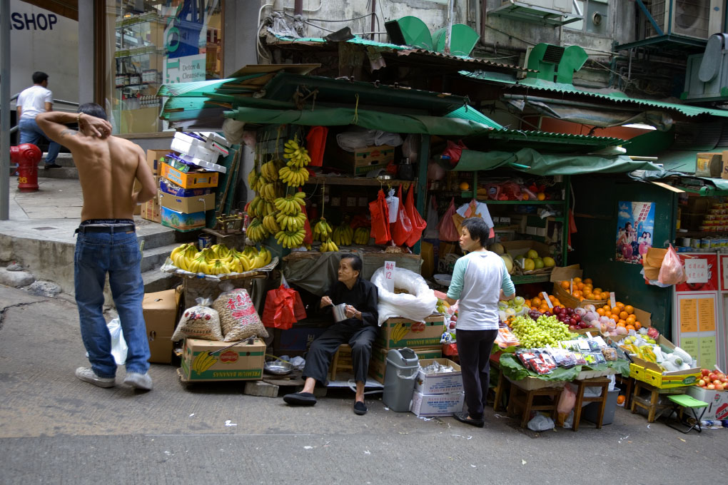 two women observe big man from their produce stall Pottinger St, Hong Kong