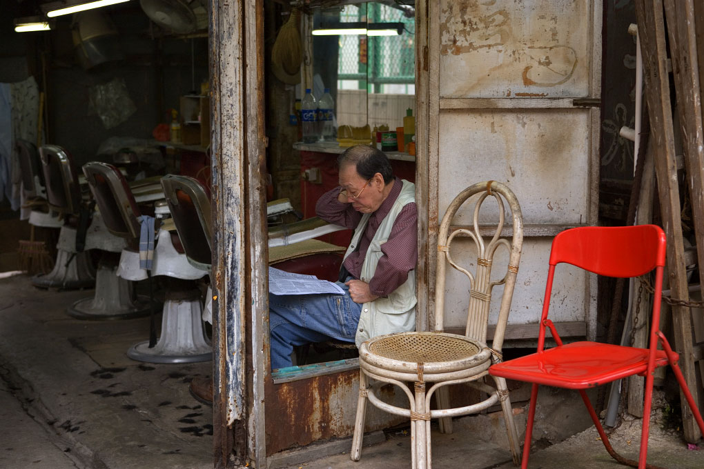 barber reading the racing form in his empty shop Sheung Wan, Hong Kong