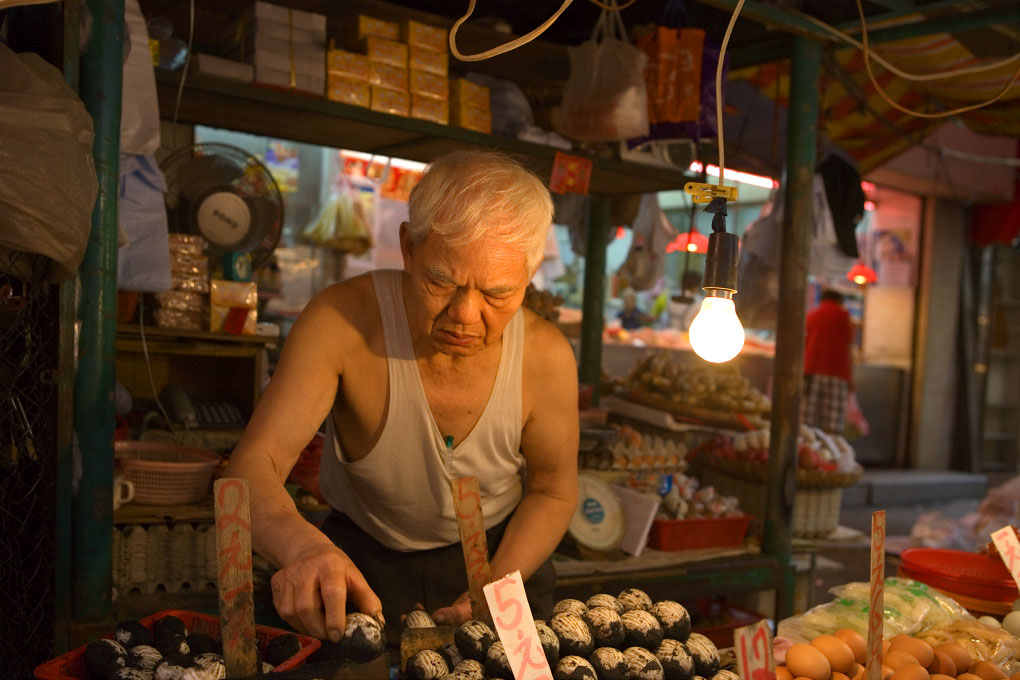 vendor carefully stacking eggsat a stall in Wan ChaiHong Kong