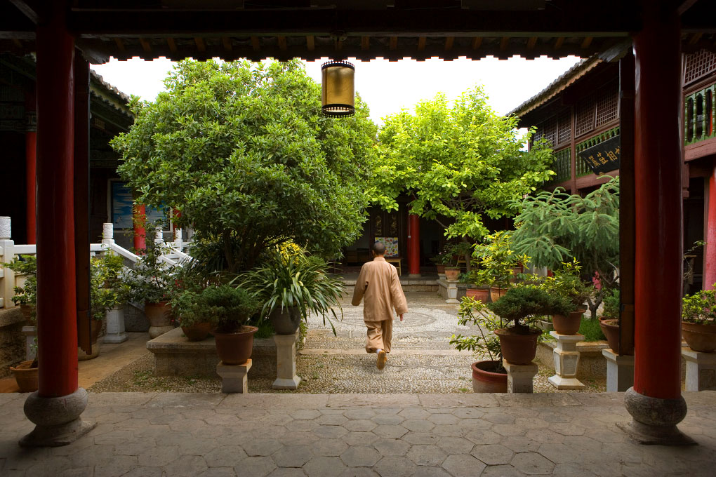 monk walking through monastery courtyardOld Town - Lijiang, China
