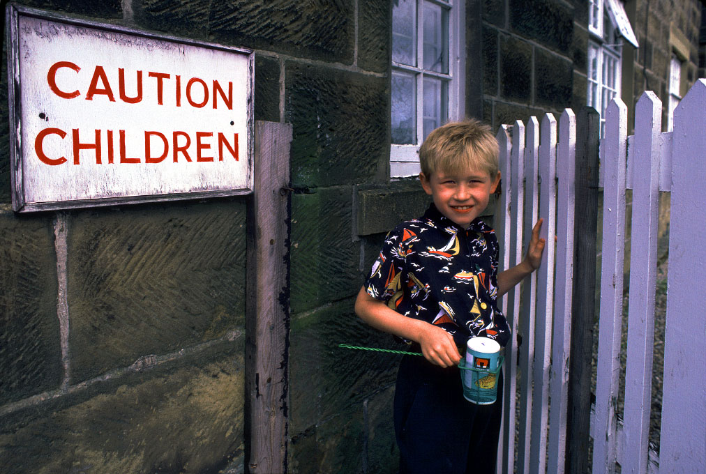 boy at gate with fish to feedNorth York Moor, England