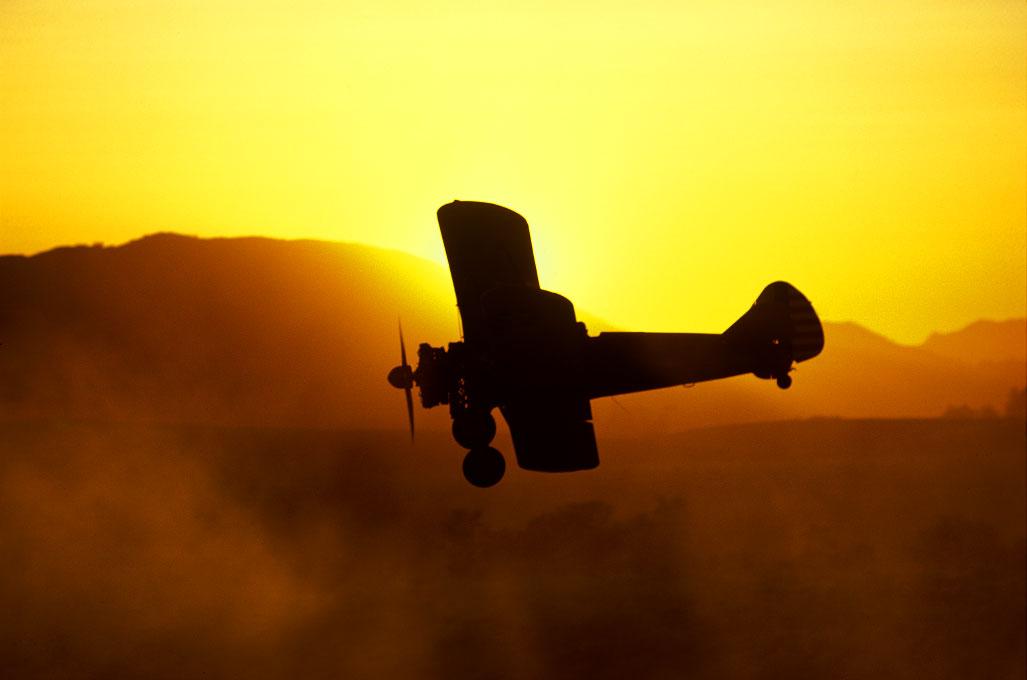 biplane banking into a sunsetover Napa Valley, California