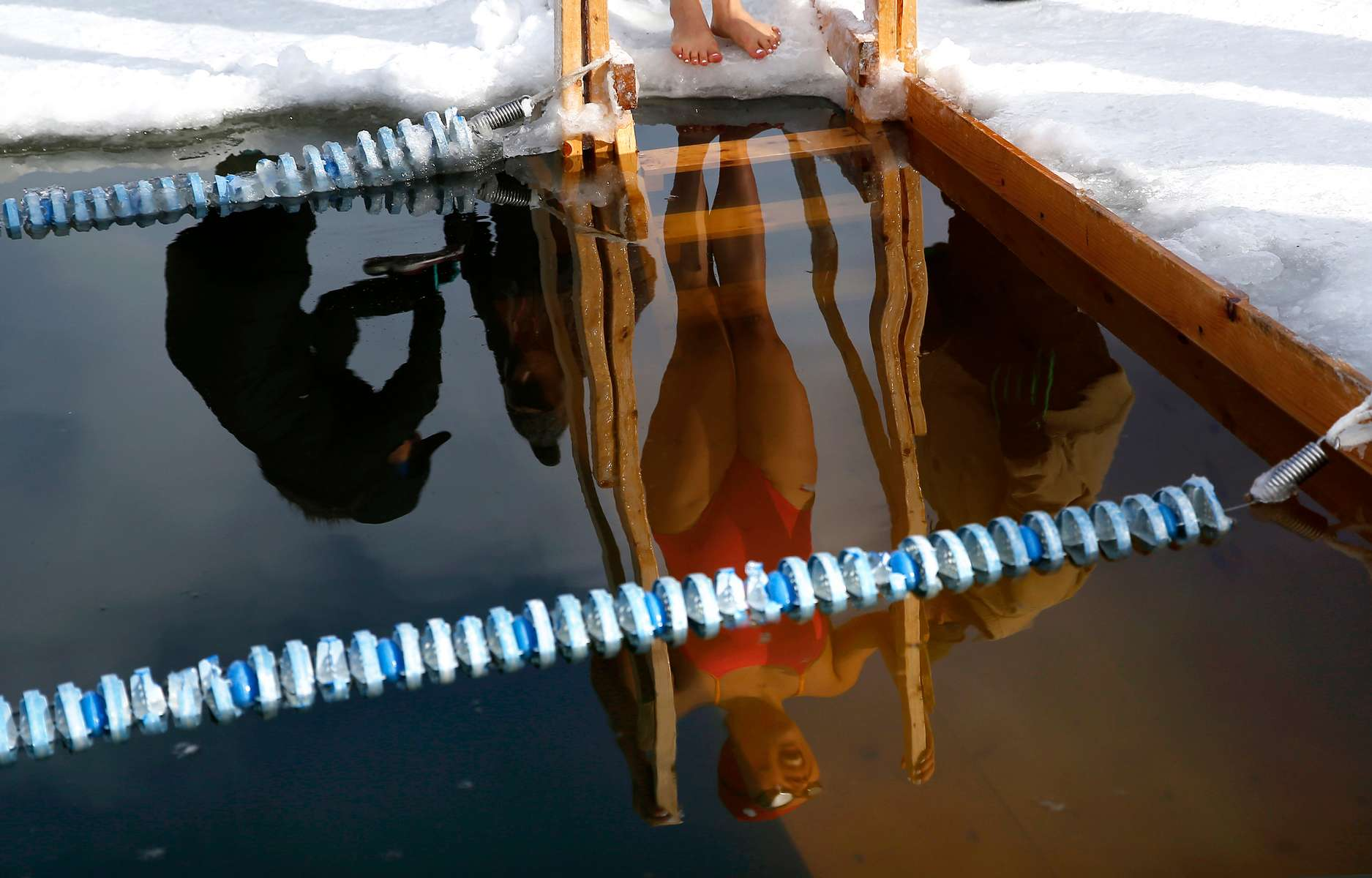 Newport, VT - 3/1/20 -  Qing Li, of Chicago stands ready at the steps of the pool as she waits to compete in the 100 meter freestyle in 28 degree water during the Winter Swim Festival at Lake Memphremagog.