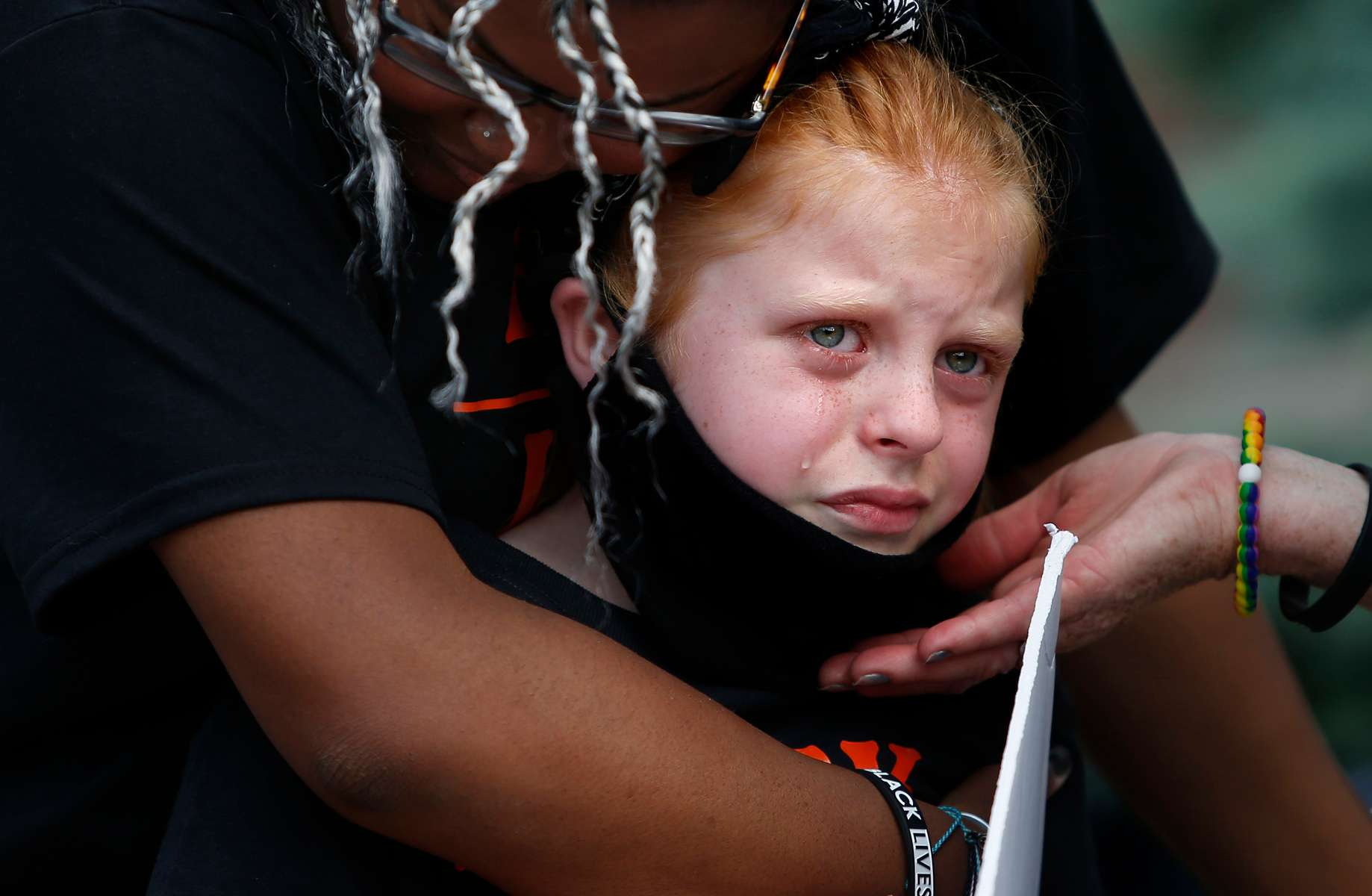 Woburn, MA - 6/4/20 - Valentina Manna, 8, (C) is comforted by her sister, Ty, 16, (L) after she took the microphone to speak to a crowd gathered at a peaceful Black Lives Matter vigil to honor the life of George Floyd and told the crowd, {quote}I don't care what color my sisters' skin is because I love them.{quote} Valentina broke down in tears and was embraced by her two sisters Brooklyn and Ty.