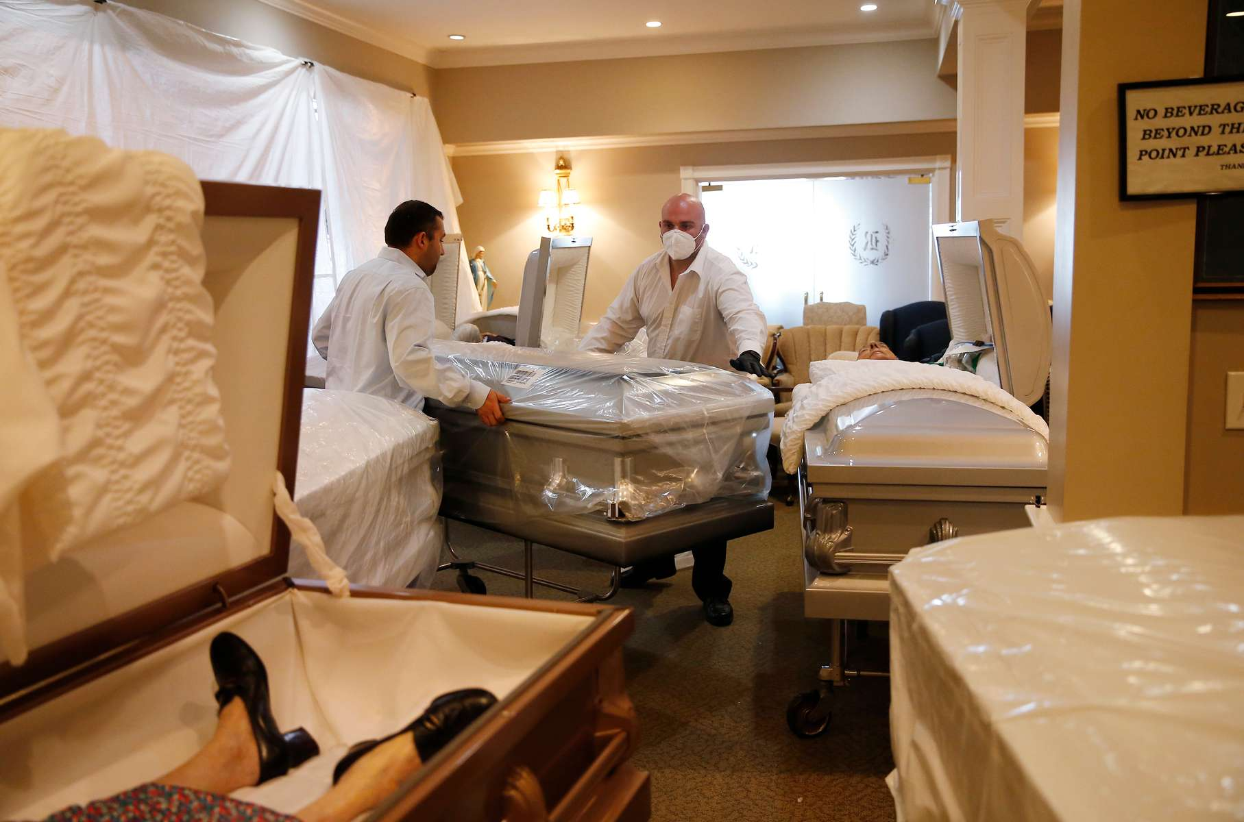 East Boston, MA - 4/28/20 -  Funeral director Joe Ruggiero, the second generation to run his family's business, and apprentice funeral director Nick Verrocchi, (R) move a casket inside a makeshift storage area. In normal times the room is used as a tribute room where families could gather, have some coffee and regroup but with a surge in COVID-19 deaths, the room had to be temporarily repurposed. (Jessica Rinaldi/Globe Staff)