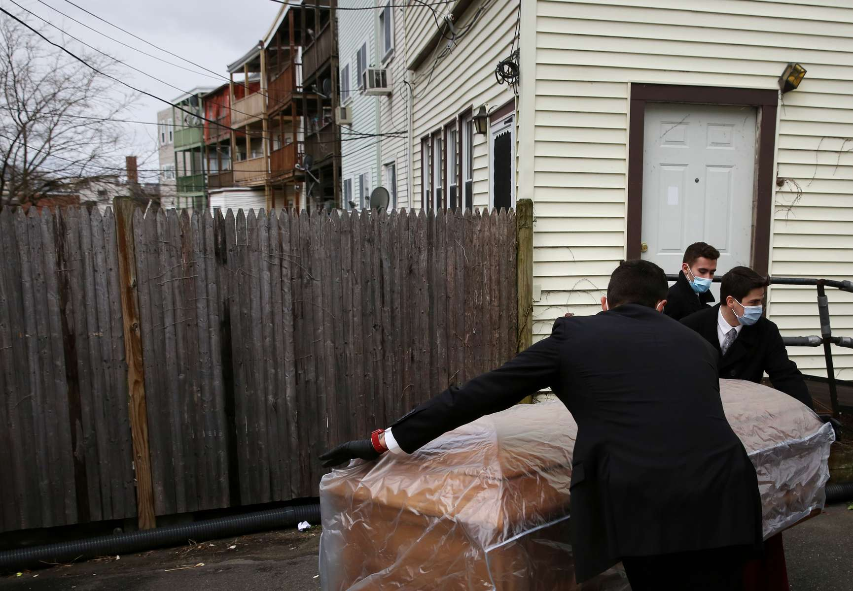 East Boston, MA - 4/28/20 -  (L-R) Matt Tauro, Nick Turco, and John Lockhead move the casket of a woman who died of coronavirus or COVID-19 to the hearse parked outside of Ruggiero Family Memorial Home. (Jessica Rinaldi/Globe Staff)