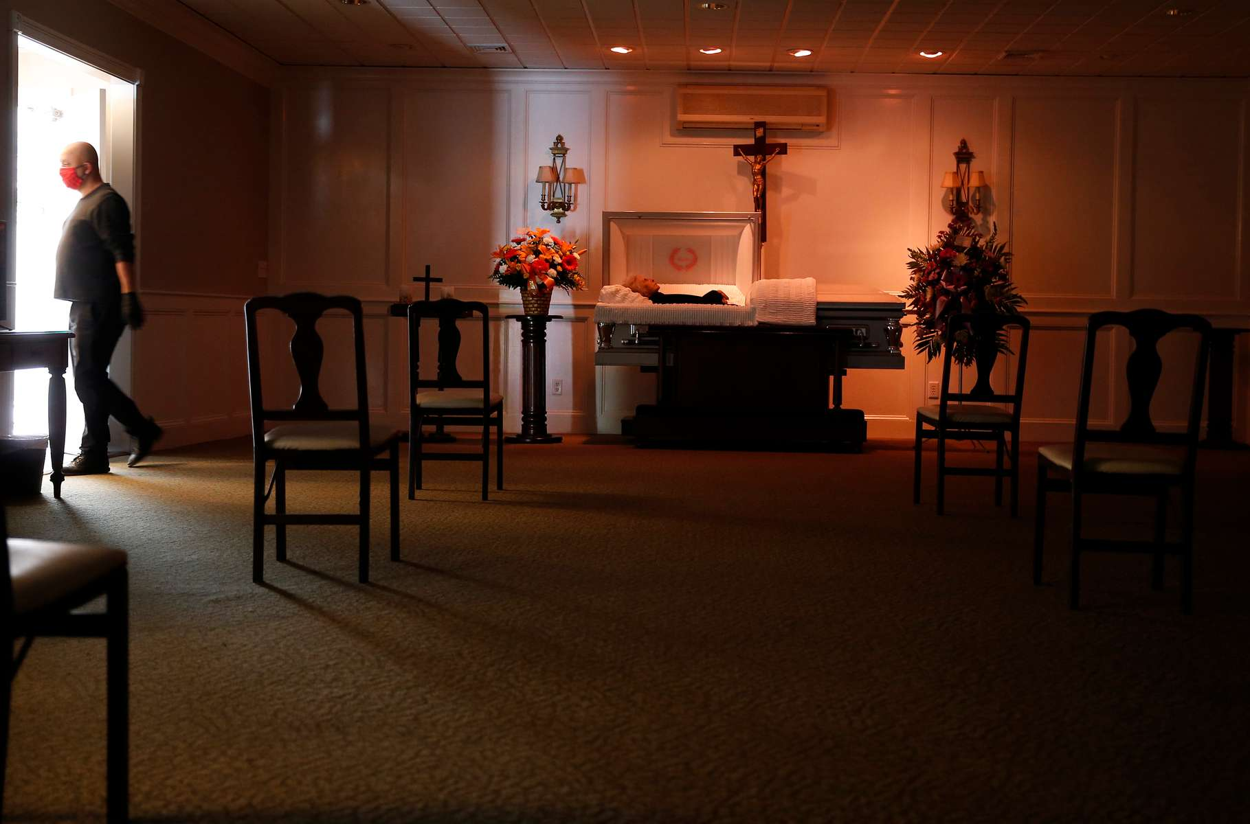 East Boston, MA - 4/28/20 - Chairs are arranged in a manner to allow for social distancing to protect against the spread of coronavirus or COVID-19 as a worker at Ruggiero Family Memorial Home in East Boston sets up for a visitation. (Jessica Rinaldi/Globe Staff)
