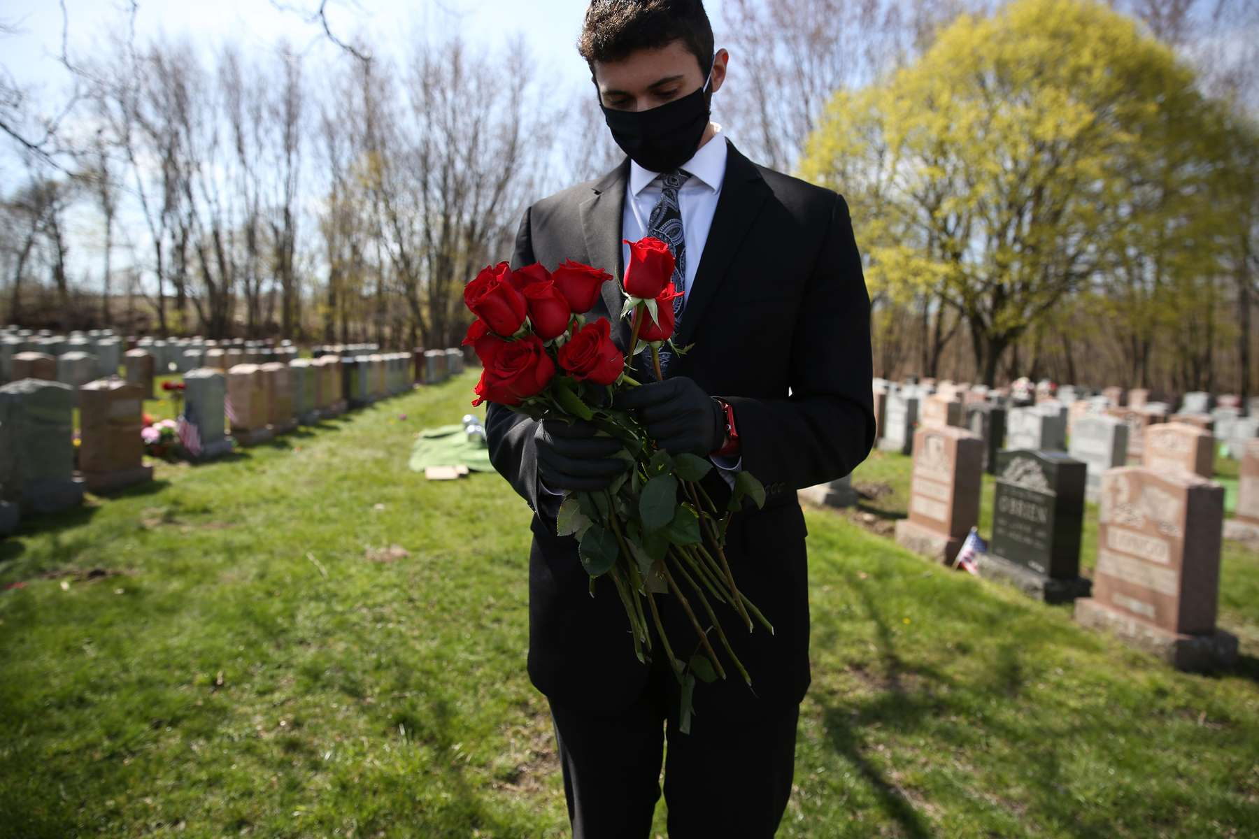 Malden, MA - 4/29/20 - Matt Tauro holds onto roses to give out to family members at Holy Cross Cemetery for Annette Nazzaro's funeral. Nazzaro, who lived to be 100, died of coronavirus or COVID-19. (Jessica Rinaldi/Globe Staff)