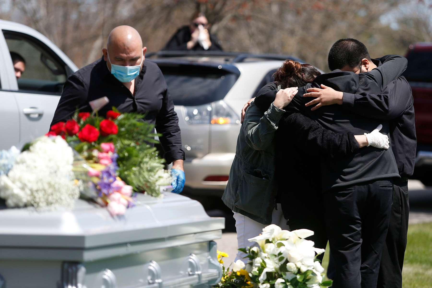 Everett, MA - 4/29/20 - Family members embrace as other mourners look on from the car during the funeral service for Santos A. Rivas at Woodlawn Cemetery in Everett. Due to strict social distancing guidelines only ten people are allowed outside of the car for graveside services at Woodlawn Cemetery in Everett. Friends and family lined three sides of the street surrounding the gravesite to pay their respects to Santos A. Rivas, who passed away from coronavirus or COVID-19. (Jessica Rinaldi/Globe Staff)